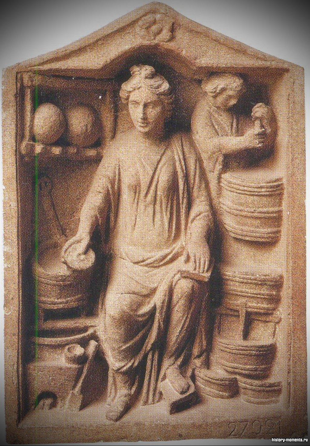 На рельефе изображена аптекарская лавка. В античные времена аптекарями обычно были женщины.